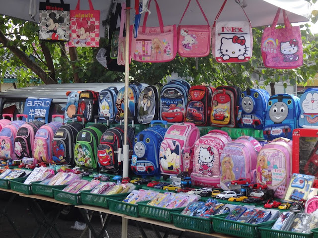 Children's school bags with different cartoon designs can be found at this morning market in Malaysia