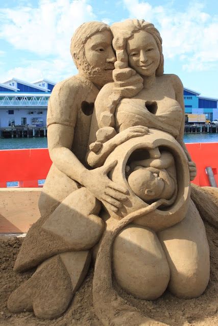 This sculpture looks real with some emotional display - A loving parents with unborn infant at Sand Sculpture Challege 2012 in San Diego, California, USA
