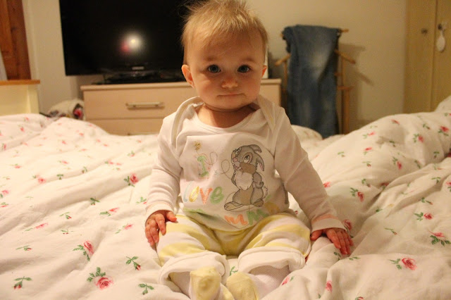 baby wearing disney pyjamas yellow and white with bunny