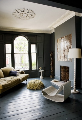 Black living room with white ceiling moulding, dark wood floors, arched windows, a green sofa, a simple fireplace and a modern sea grass chair