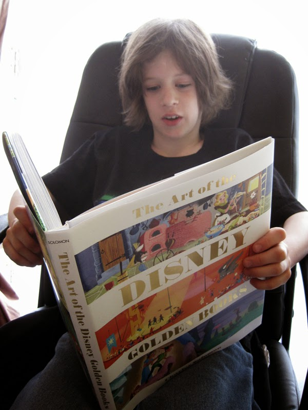 Kid reading Disney Editions book The Art of the Disney Golden Books