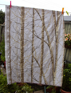 Fabric with a design of silver birch tree trunks