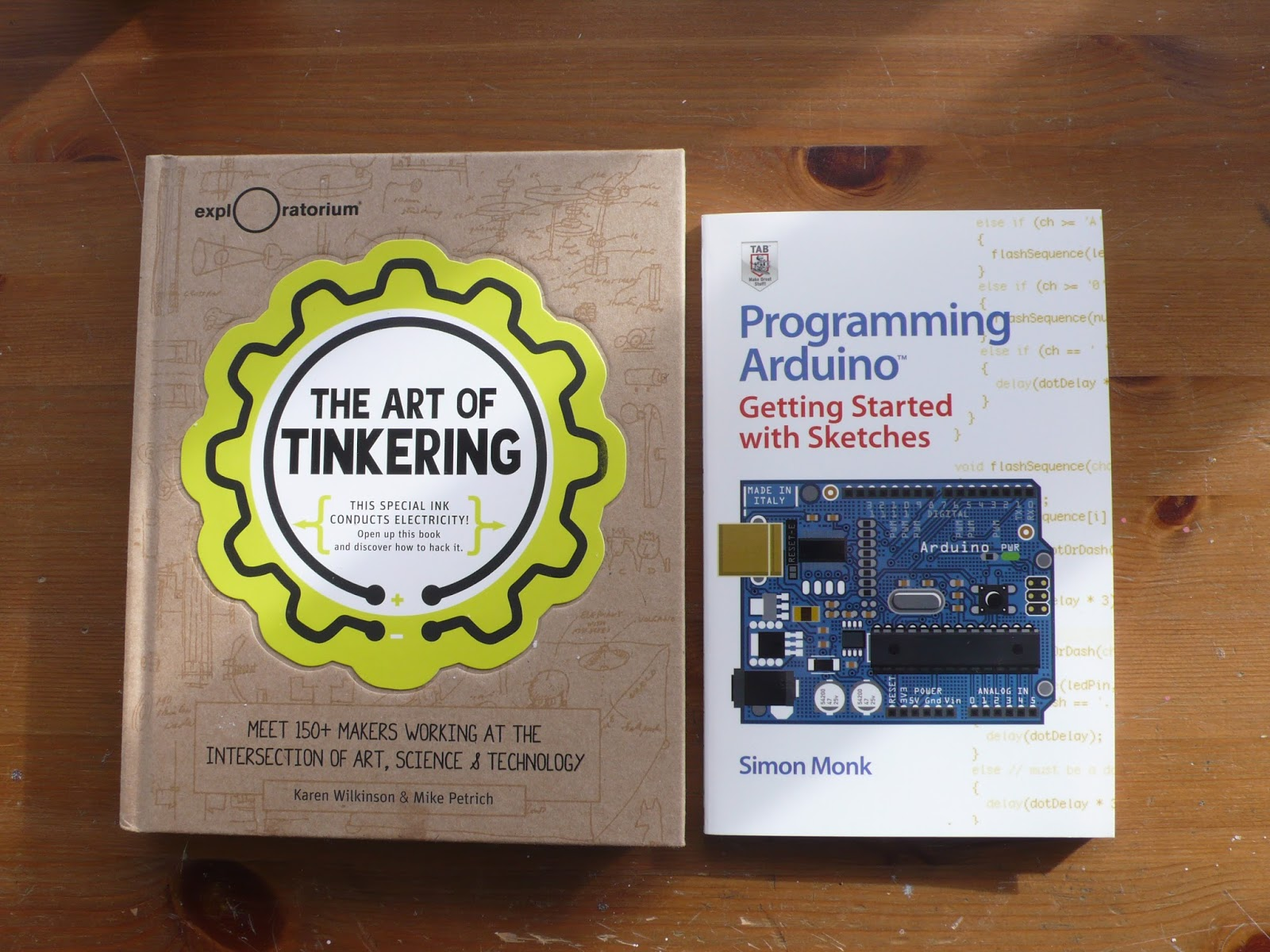 Two books, the one on the left is entitled 'The Art of Tinkering' and the other book on the right is entitled 'Programming Arduino'.