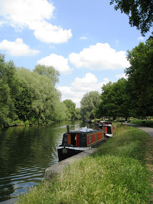 River, barges, trees, blue sky