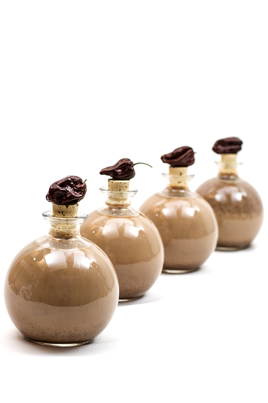 Chocolate liquor with chili bottles in row with chili