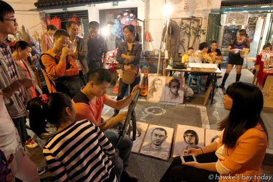 A street artist draws a portrait in one of the night markets photograph