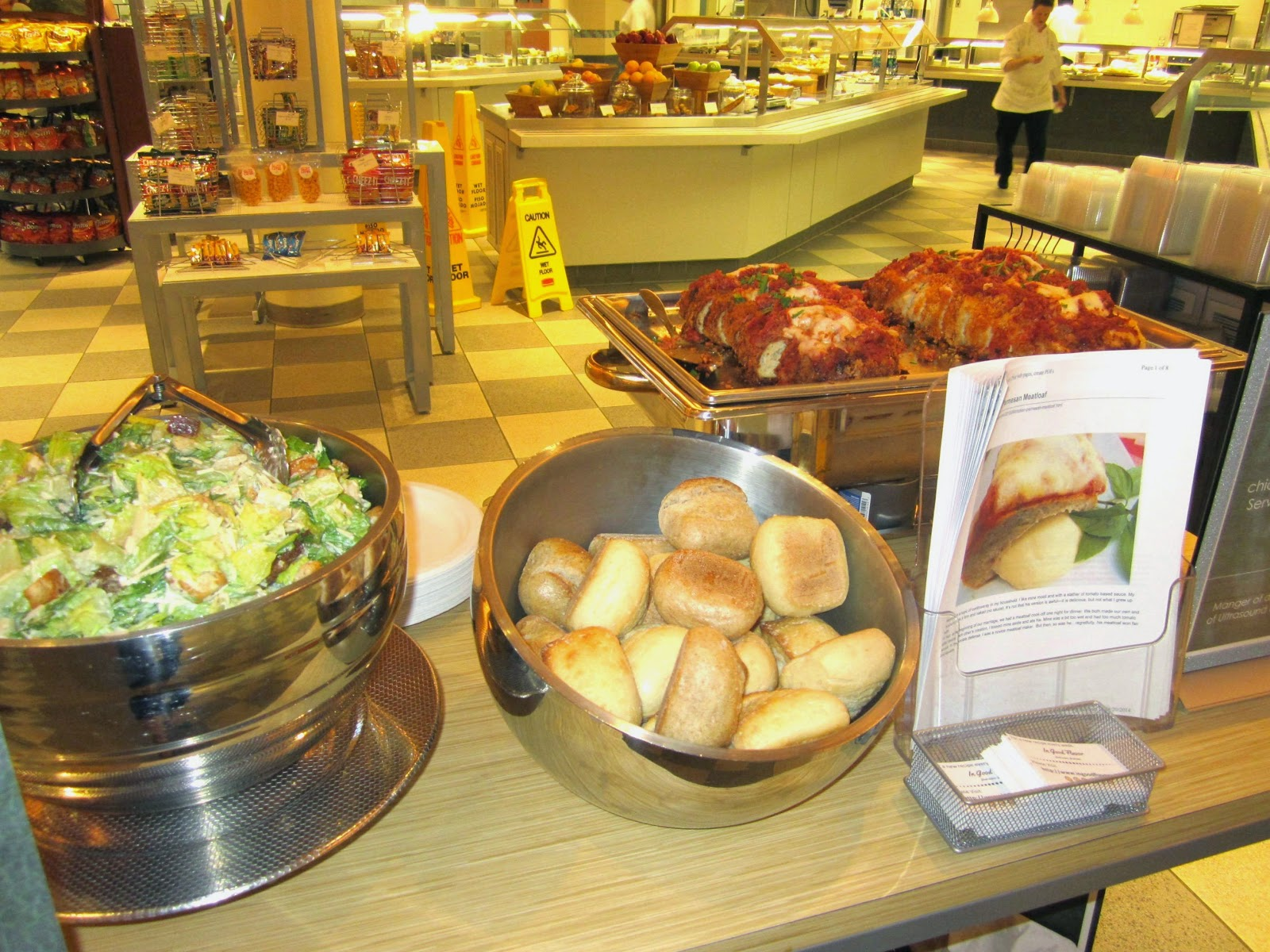 A food counter with a bowl of Ceasar salad, a bowl of  rolls, and a tray of Chicken Parmesan Meatloaf