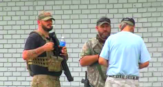 Armed Buffoons stand guard outside Save Yourself Survival and Tactical Gear (KOKI)