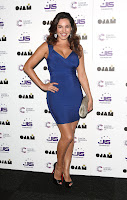 Kelly Brook posing on black carpet in a skintight dress
