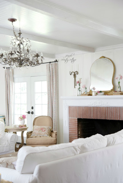 white sofas and vintage furniture in cottage living room