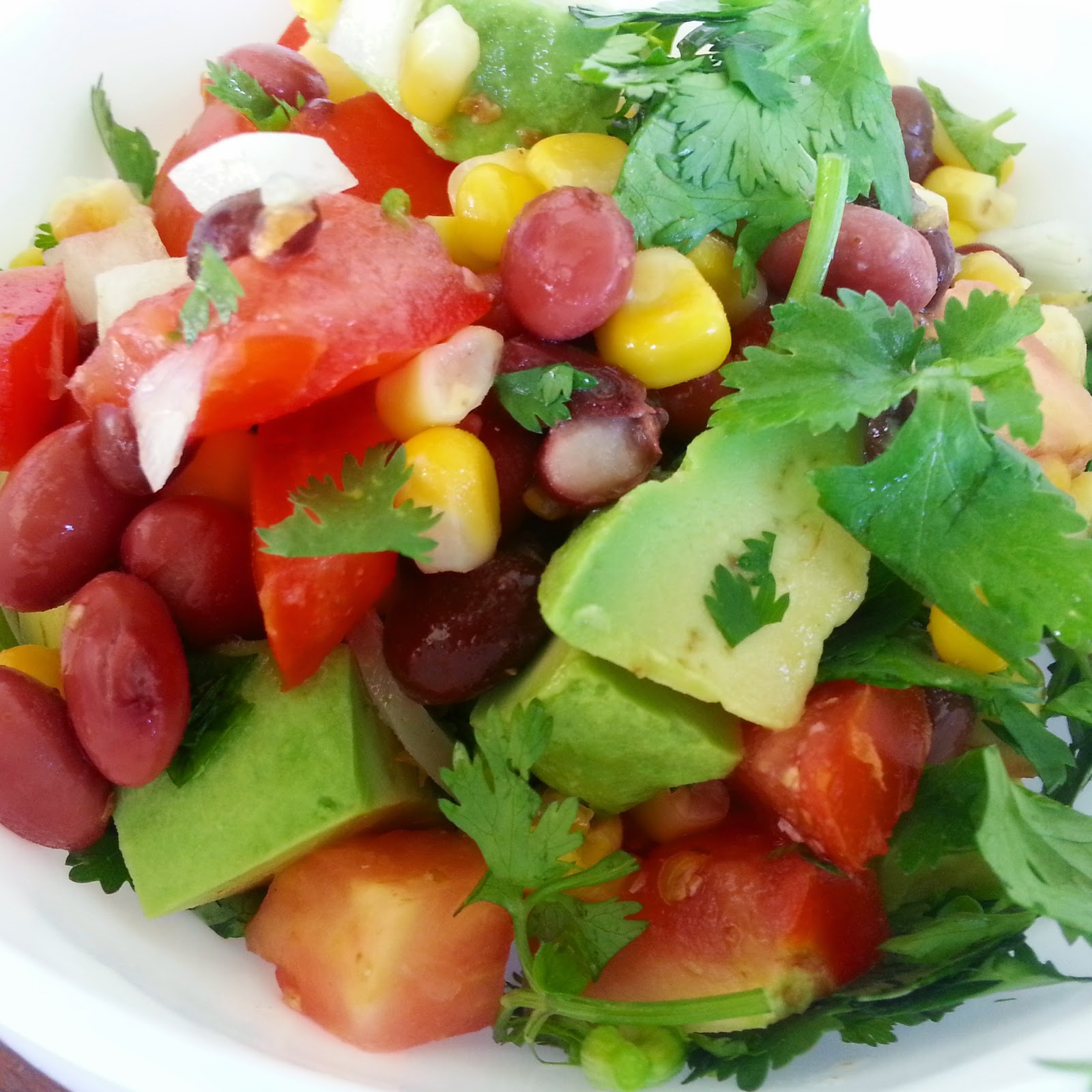 image of mexican salad with beans, corn, avocado, tomato, lime, onion and coriander
