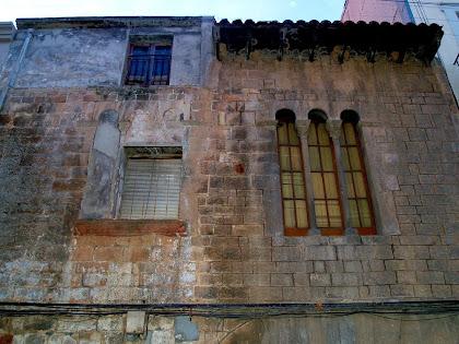 Detall del primer pis de la façana de la Casa Gausa on s'aprecien les dues finestres coronells tripartides gòtiques