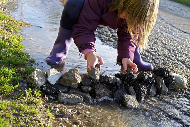 Fotografia di bambina che costruisce una diga di sassi