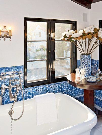 close up of blue and white bathroom tiles near black framed windows, stand alone bathtub and small round accent table
