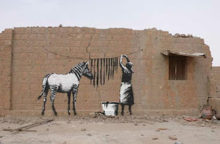 Graffiti artwork by Banksy, a zebra's black stripes are hung out to dry in the sun