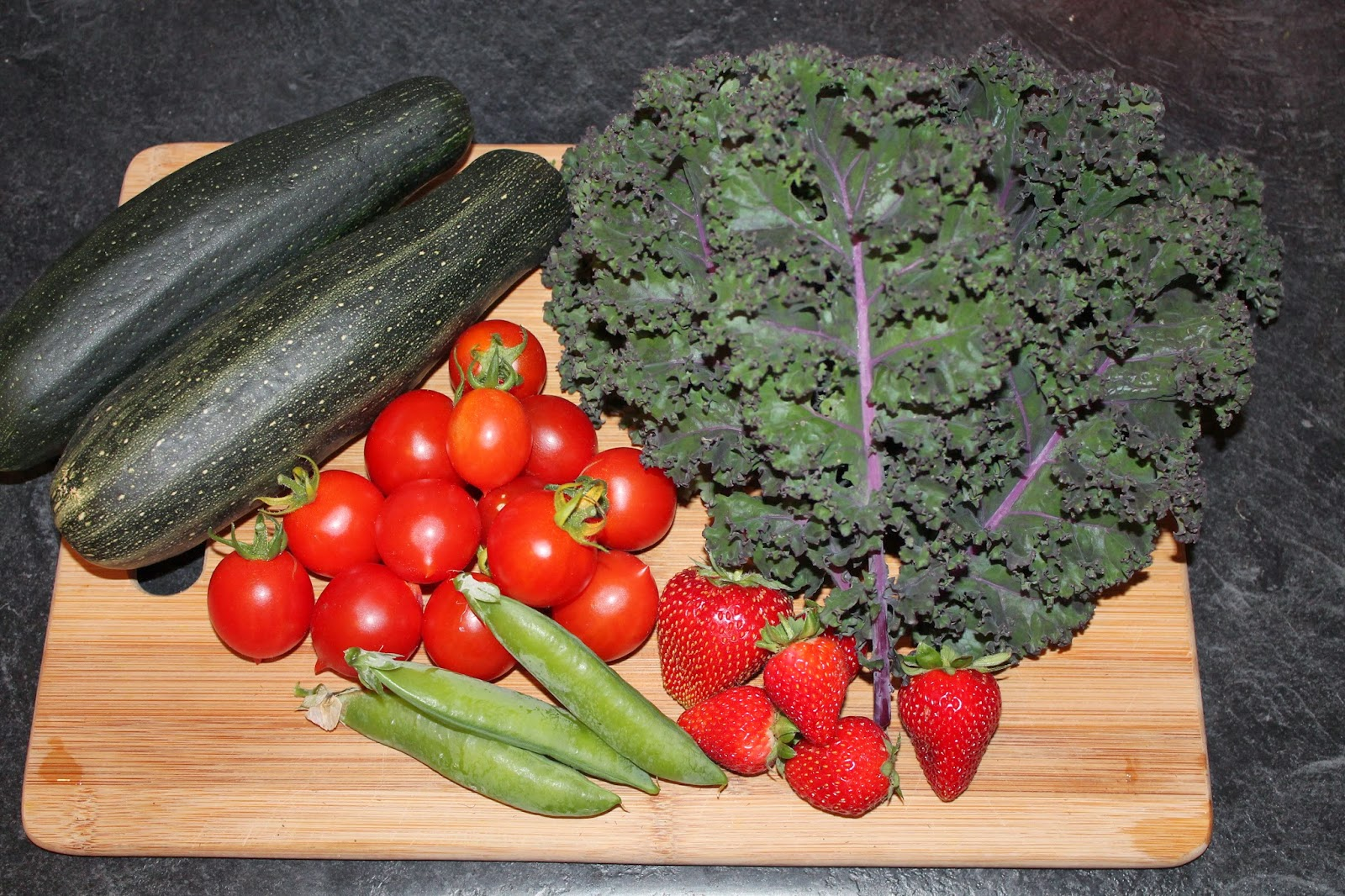 Fresh zucchini, tomatoes, peas, kale and strawberries from the garden