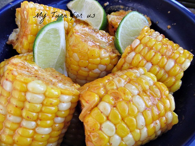 Corn on the cobb flavored with butter, chili powder and lime and ...
