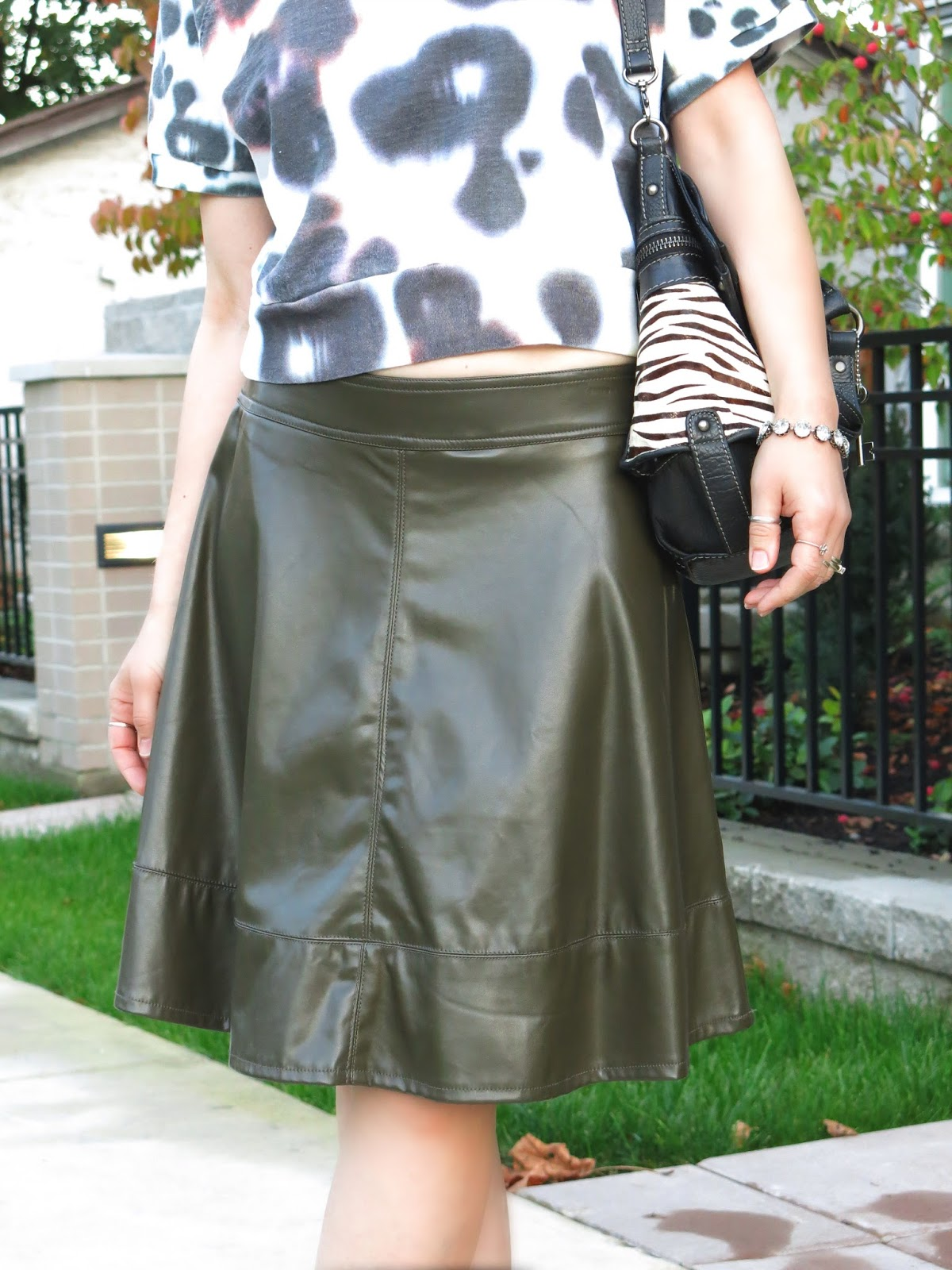 cropped patterned sweatshirt, pleather skater skirt, and zebra-striped Fossil bag