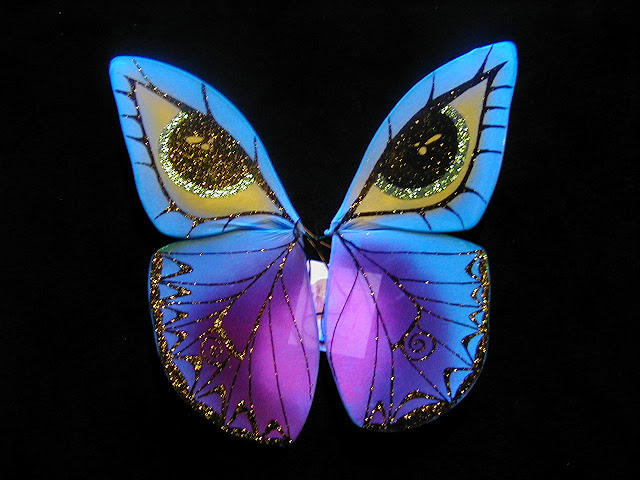 flourescent baby blue and pink and purple butterfly wings with sparkly blue eyes and shiney black veins