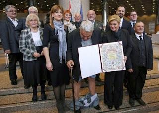 وقَف مع رئيسة كرواتيا الجميلة لاستلام جائزة  فسقط منه بنطاله.. شاهد ماذا فعل