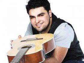 cantor Kadu Quintanhilha segurando um violão