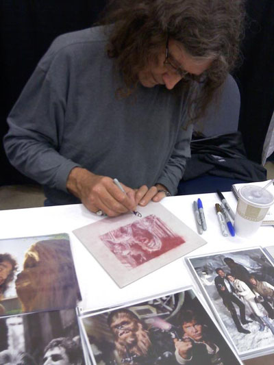 Peter Mayhew signs an original piece of art by Jeff Lafferty