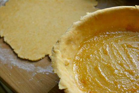 Confituurtaart maken: bedek bodem en rand van een taartvorm met deeg en strijk een laag abrikozengelei over de bodem