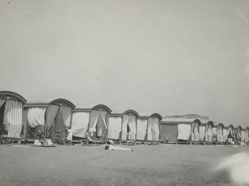A long row of beach cottages on a dutch beach on a picture in the Rijksmuseum