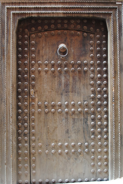 Antique studded Moroccan front door with carved frame - The Doors Of Marrakech Find, Buy And Renovate A Riad In Marrakech