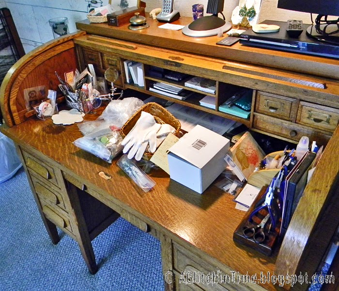 Clutter on Oak roll-top desk