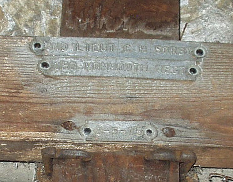 "The centre portion of a wooden cross, on the junction are three rivetted metal plates bearing the text ""2nd Lieut CM Sorby, 3rd Monmouthshire Regt, 8-5-15""."
