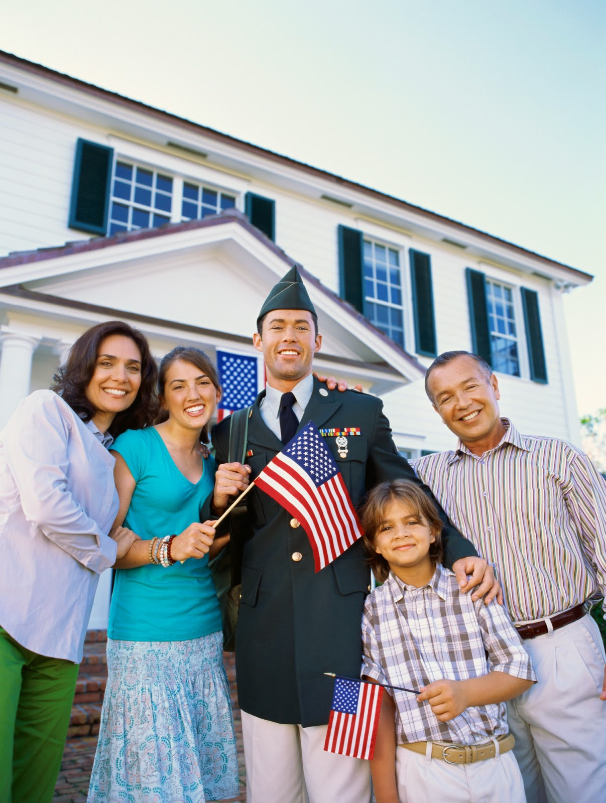 military serviceman holding flag, surrounded by family.