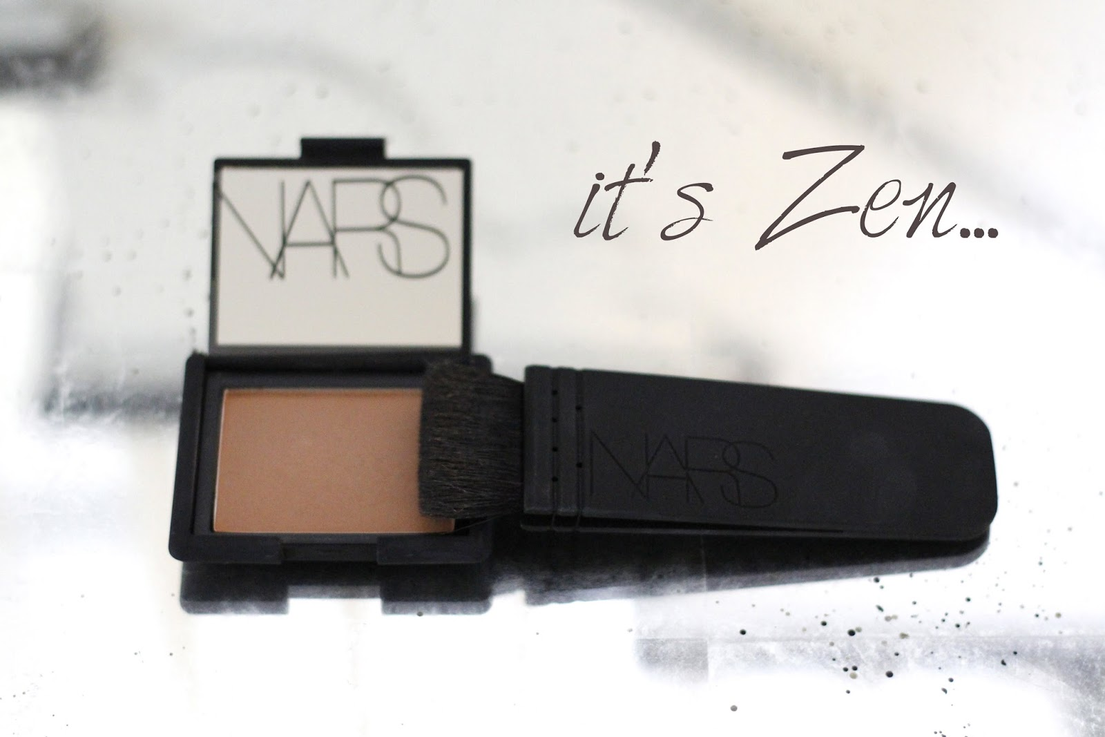close-up of NARS blush in 'Zen' and NARS Artisan Kabuki Contour brush