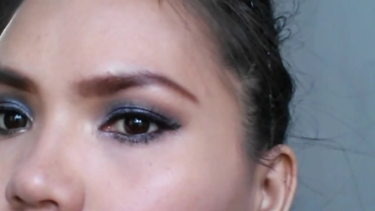 Black Smokey Eyes Makeup Tutorial. Lady showing her final makeup