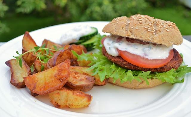 Foto av en hvit asjett med burger på den høyre siden og 7-8 gylne potetbåder på venstre siden. Burgeren har hjemmelaget burgerbrød som ser litt rustikt ut, og har sesamfrø på seg. Det er også en vegansk yoghurtdressing rett under det øverste burgerbrødet. Under dressingen er en tomatskive, og deretter selve burgeren, før et rapidsalatblad avslutter komposisjonen. I bakgrunnen kan vi skimte grønne planter, som er ute av fokus.