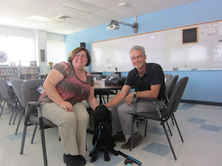 Michele, Coach and Jeff are sitting by in one of the English classrooms where we had our meeting.Coach is on the floor.  Michele and Jeff are in chairs.