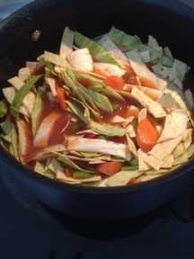 Image shows Tomato Cabbage Soup in the big soup pot before the lid goes on and it starts to simmer.