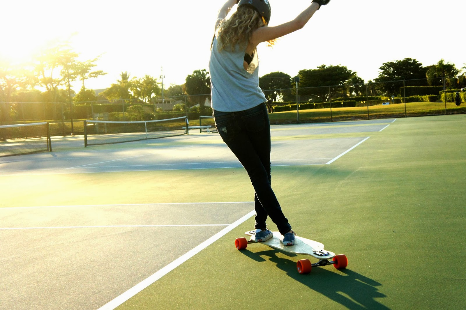 Sunny longboarding style girl tennis court