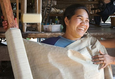 This Thai silk weaver enjoys the benefits of being a member of a weaving co-operative as she proudly displays her sumptuous silk fabric.
