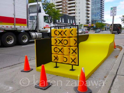 Bright yellow slide in parking spot on Lakeshore Road, Port Credit, with abacus of Xs and Os.