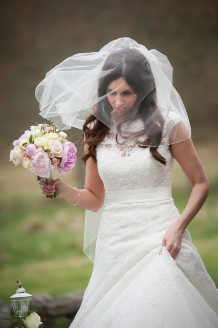 Bride wears a blushing veil and hold a bouquet on her way to the ballroom at Glen Tanar Estate in Aberdeenshire