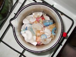 SZöveg: Ebben csak egy kis piros illatos gyertyamaradék van, a nagyja inkább fehér. Ha színes gyertyát szeretnél és csak fehéred van, egy kis rúzzsal színezheted (beletörsz egy darabkát a megfelelő színű rúzsból és az edényben a többivel összeforralod). Állítólag zsírkrétával is lehet színezni, habár ezt nem próbáltam. Kép: aragáz (gáztűzhely) csücskéje fentről fényképezve. Az egyik égőn egy csőrös edényben apróbb gyertyadarabkák vannak beletéve.