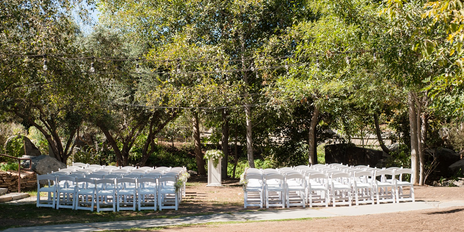 The Ceremony Was Set Up Under A Canopy Of Trees With Jars Baby Breath And Mums Hanging Along Aisle For Delicate Touch Color