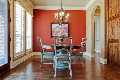 traditional style dining room with classic dining furniture and chandelier having a red backdrop
