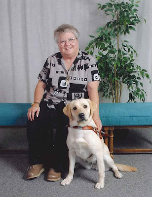Evelyn Burris sits next to her yellow Lab Guide Dog, Colusa, on a bench