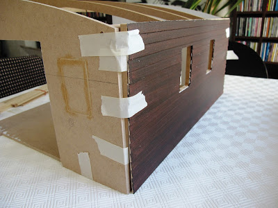 A half-built dolls' house shed, with weatherboard cladding masking taped onto the rear wall.