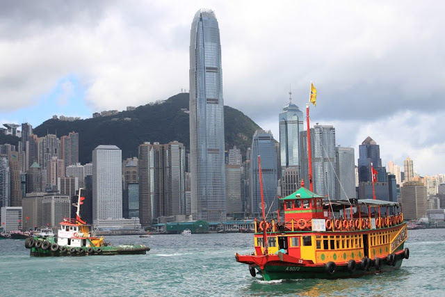 Hong Kong skyscrapers with Chinese junk ship sailing by in Hong Kong