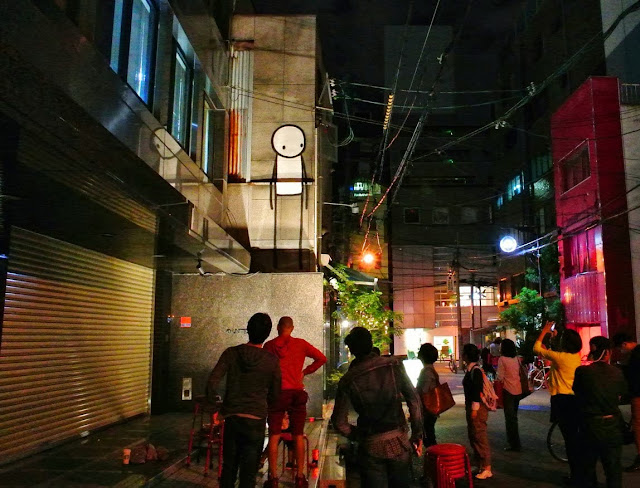 British Street Artist Stik paints a new street piece on the streets of Osaka, Japan. 1