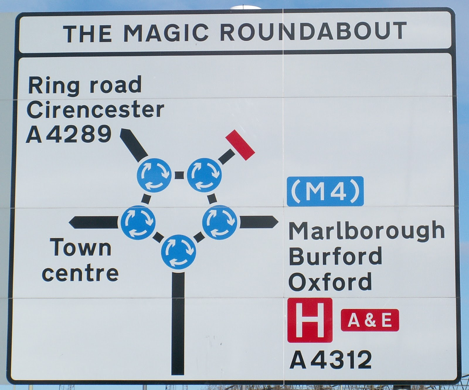 Road sign for the Magic Roundabout, showing a central roundabout surrounded by five smaller satellite mini-iroundabouts