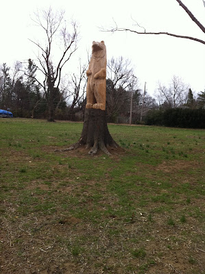 bear carved from the stump of a tree standing on the rest of the stump